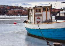 Fiskebåt med en blå skrov som förtöjas på en djupfryst flod i vinter royaltyfri fotografi
