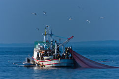 Fiskebåt med reden på havet framme av berget Athos Arkivbild