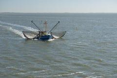 Fiskebåt nära stranden på det holländska Wadden havet Arkivbild