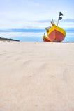 Fiskebåt på den sandiga stranden för baltiskt hav med dramatisk himmel under sommartid Arkivfoton