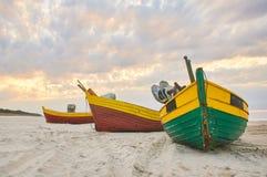 Fiskebåt på den sandiga stranden för baltiskt hav med dramatisk himmel under sommartid Royaltyfria Bilder