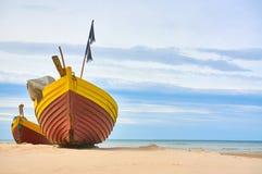 Fiskebåt på den sandiga stranden för baltiskt hav med dramatisk himmel under sommartid Arkivbilder