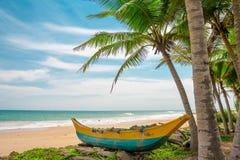 Fiskebåt på en härlig strand arkivfoton