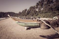 Fiskebåt på en tropisk strand med palmträd i backgrouen Royaltyfri Fotografi