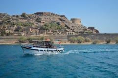 Fiskebåt på havet med den Spinalonga ön och fästningen i bakgrunden Royaltyfria Bilder