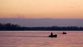 Fiskebåt på solnedgången på floden stock video