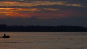 Fiskebåt på solnedgången på floden arkivfilmer