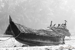 Fiskebåt på stranden mot djungelbakgrund svart white Fotografering för Bildbyråer