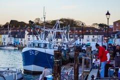 Fiskebåt på Weymouth av att ladda fiskhamnen royaltyfri bild