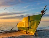 Fiskebåt som ankras på den sandiga stranden under subrise Fotografering för Bildbyråer