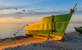 Fiskebåt som ankras på den sandiga stranden under subrise Royaltyfria Foton