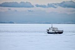 Fiskebåt som frysas i isen royaltyfria foton