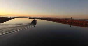 Fiskebåt som långsamt flyttar sig under soluppgång arkivfilmer