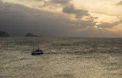 Fiskebåt som skriver in under solnedgång, till porten av Aviles royaltyfria foton