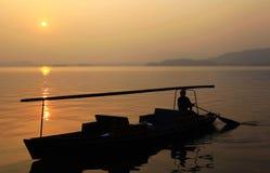 Fiskebåt under solnedgången arkivbild