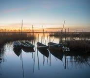 Fiskebåtar förtöjde på den lilla träbron över floden Royaltyfria Bilder