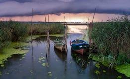 Fiskebåtar förtöjde på den lilla träbron över floden Arkivfoton