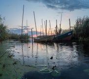 Fiskebåtar förtöjde på den lilla träbron över floden Arkivbilder