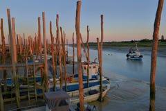 fiskebåtar i en farled på lågvatten på solnedgången royaltyfria foton