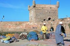 Fiskebåtar, kugghjul och fiskare på bakgrund av Castelo som är verklig av Mogador royaltyfria foton