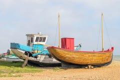 Fiskebåtar på stranden och som lämnar för att ruttna Arkivbild