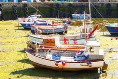 Fiskebåtar på tidvatten ut Arkivbild