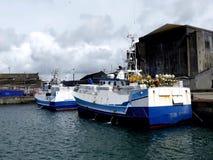Fiskebåtar som anslutas på pir Arkivfoto