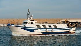 Fiskebåten går tillbaka till port Arkivfoto