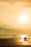 Fiskebåtsoluppgång med motorcykeln Arkivfoton