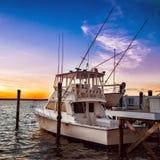 Fiskebåtyacht på pir på solnedgången på sjöpir royaltyfri foto
