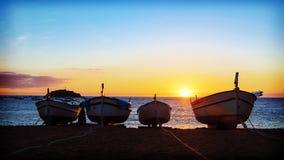 Fiskebåtar i medelhavet på soluppgångbakgrund Arkivbild