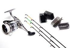 Fiskeförlagematare och rulle med tillbehör på vit bakgrund Arkivbild