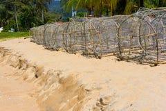 Fiskekorgen förtjänar på stranden Royaltyfri Foto