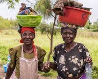 2017 fiskeläge för Sept 7, Lake Victoria, Kisumu län, Kenya, Afrika Afrikanska kvinnor med fulla hinkar balanserade på deras huvu royaltyfria foton