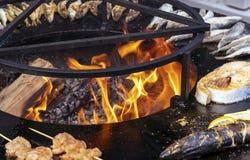 Fisken och annan skaldjur stekas på ett runt galler arkivfoton