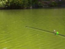 Fiskepolen med klockor i gör grön den lugna floden, nedersta rev Arkivfoto