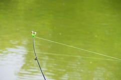 Fiskepolen med klockor i gör grön den lugna floden, nedersta rev Arkivbild