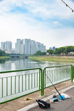Fiskepoler med floden och byggnader i bakgrund arkivbilder