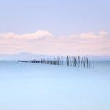 Fiskepoler och mjukt bevattnar på havet landskap. Lång exponering. Arkivbilder
