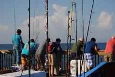 Fiskepoler på en solig dag på pir Royaltyfri Bild