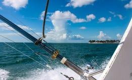 Fiskepoler på fiskebåten för djupt hav med sikt av ön i avstånd under blåa himlar med fluffiga vita moln arkivbild