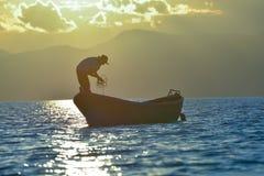 Fiskeriarbete och soluppgång; funktionsduglig man Arkivfoton