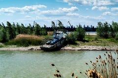 Fiskeskonare på fjärden bland cattails Arkivfoto