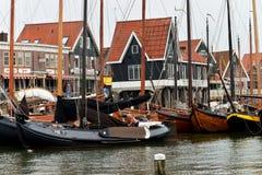 Fiskeskyttlar och på bakgrundsfiskauktionen i hamnen av Volendam, Holland Arkivfoto
