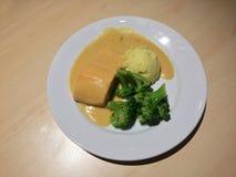 Fiskkött som överträffas med sås och kokaad broccoli, en skopa av, mosar potatisen i den vita maträtten royaltyfria foton
