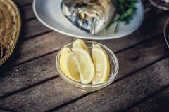 Fiskmat på den vita plattan med citronen Arkivbild