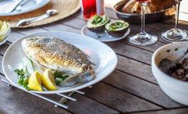 Fiskmat på den vita plattan med citronen Fotografering för Bildbyråer