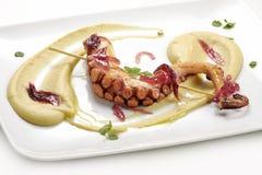 Fiskmaträtt, bräserad bläckfisk på kikärtkräm med caramelized på Arkivfoto