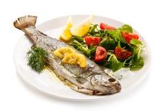 Fiskmaträtt - grillad forell med grönsaker arkivbild