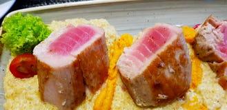 Fiskmaträtt: grillad tonfisk i en säng av potatisar med tomater och sallad royaltyfria foton